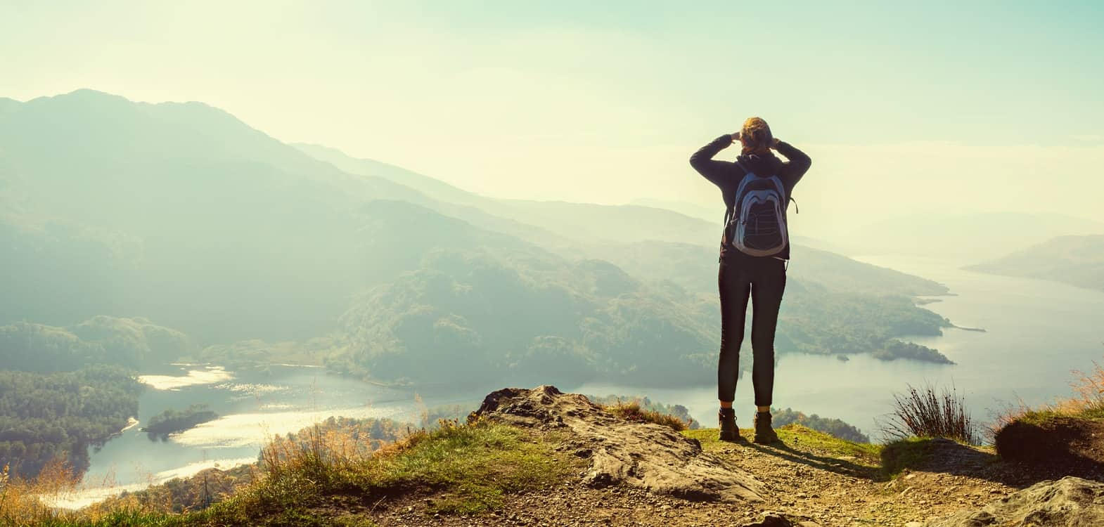 woman with arms up to face looking out across the Scottish Highlands whilst high up on a hill