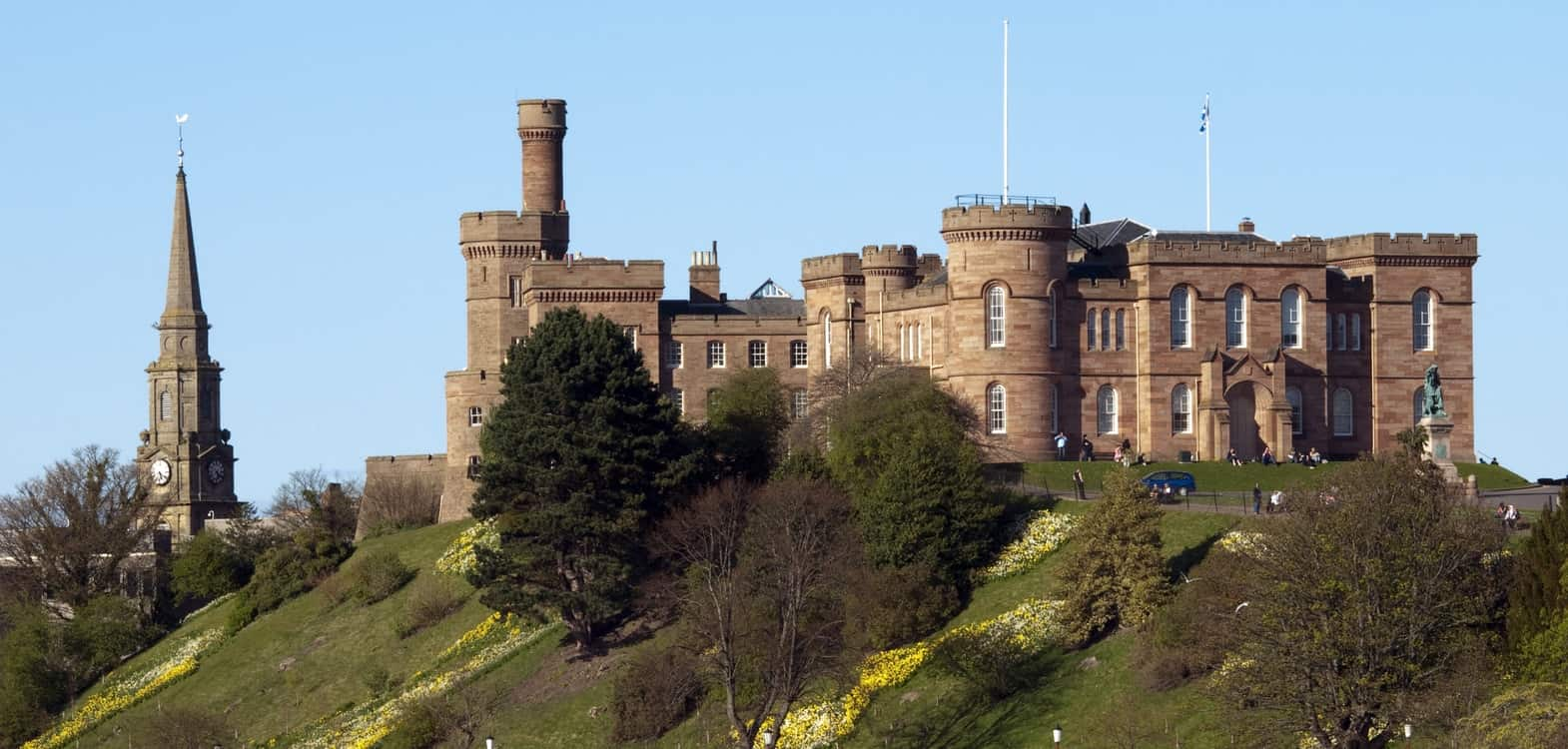 View of Inverness Castle on Castle Hill in Inverness with a blue sky background and slopes with daffodils