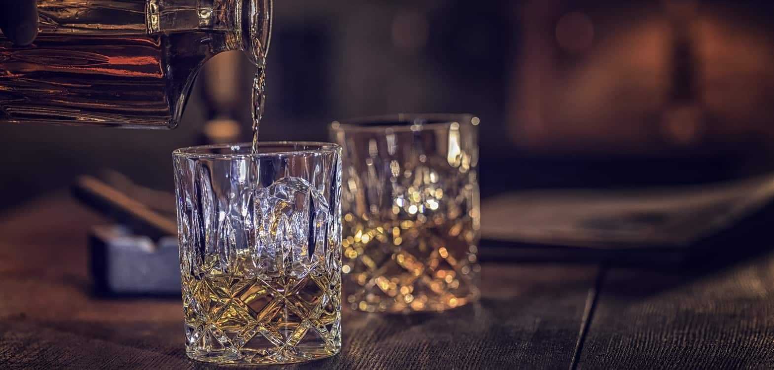 Bottle of Scottish whisky being poured into Edinburgh Crystal cut glass tumbers