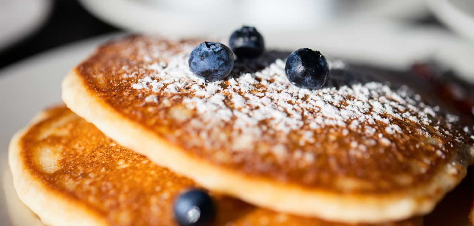 stack of pancakes with powdered sugar and blueberries - a special breakfast at Firhall B&B