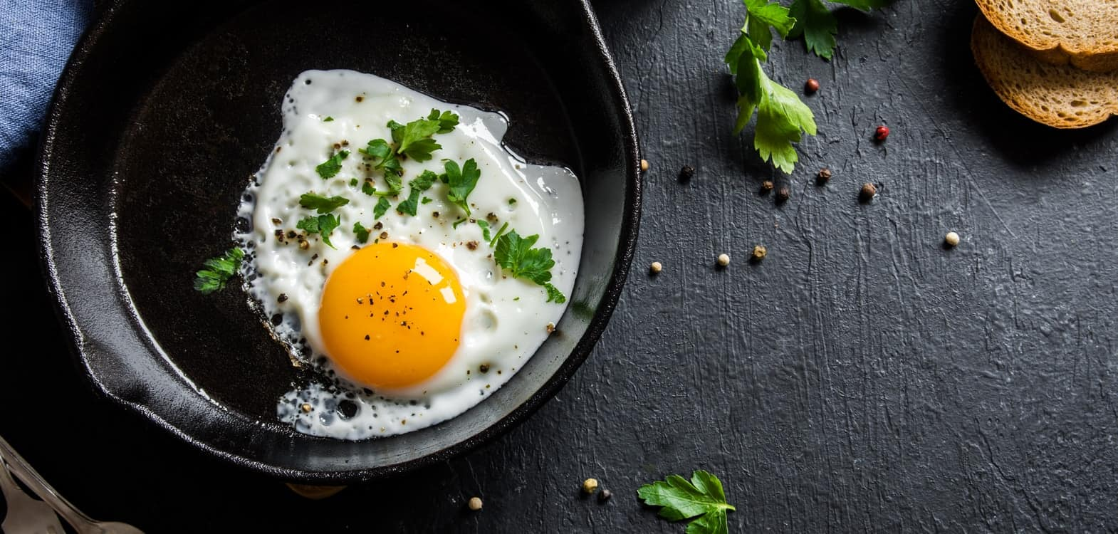 Fried egg in a black cast iron frying pan with fresh herbs sprinkled over the egg, breakfast at Firhall Bed & Breakfast