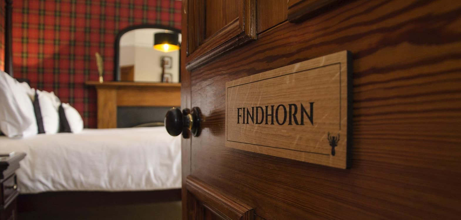 Findhorn door sign leading into the bedroom at Firhall Highland B&B onto bed with white bed coverings