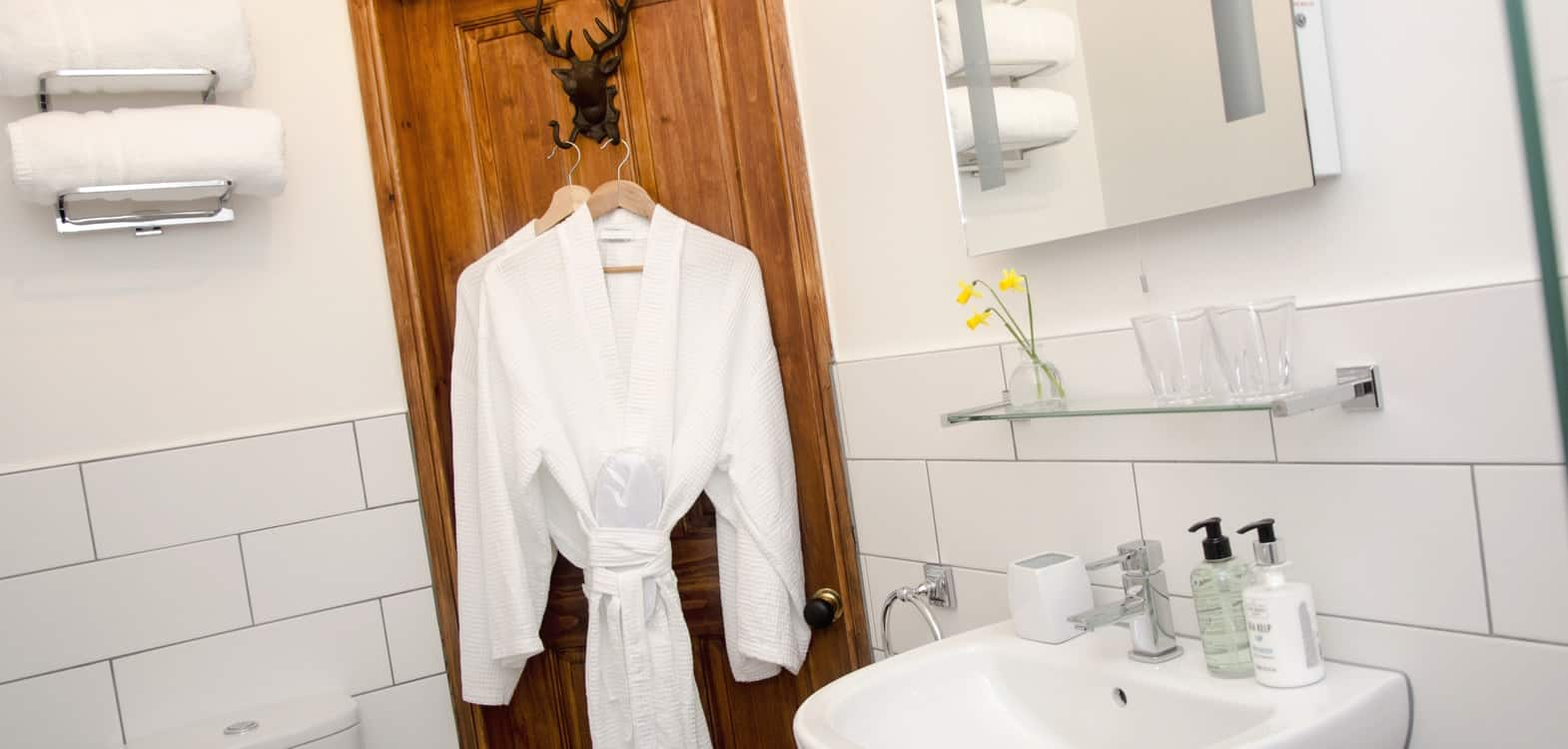 white cotton bathrobes hanging on thee back of a bathroom door in a white tiled bathroom with white sink