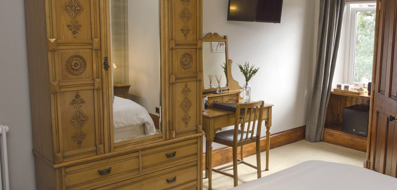 Mirrored and carved wardrobe doors with drawers underneath in the Harris bedroom at Firhall B&B
