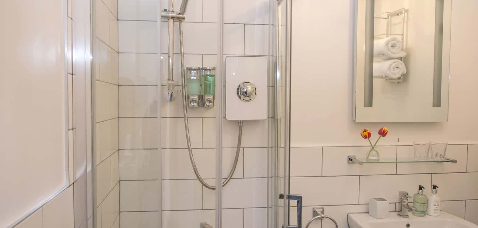 Shower cubicle showing white bathroom suite and heated mirror at Firhall B&B Scotland
