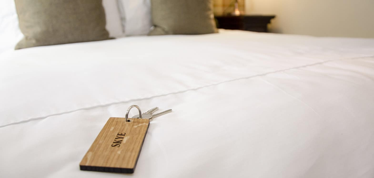 Room key for Firhall Bed and Breakfast on a wooden key fob placed on a a bed