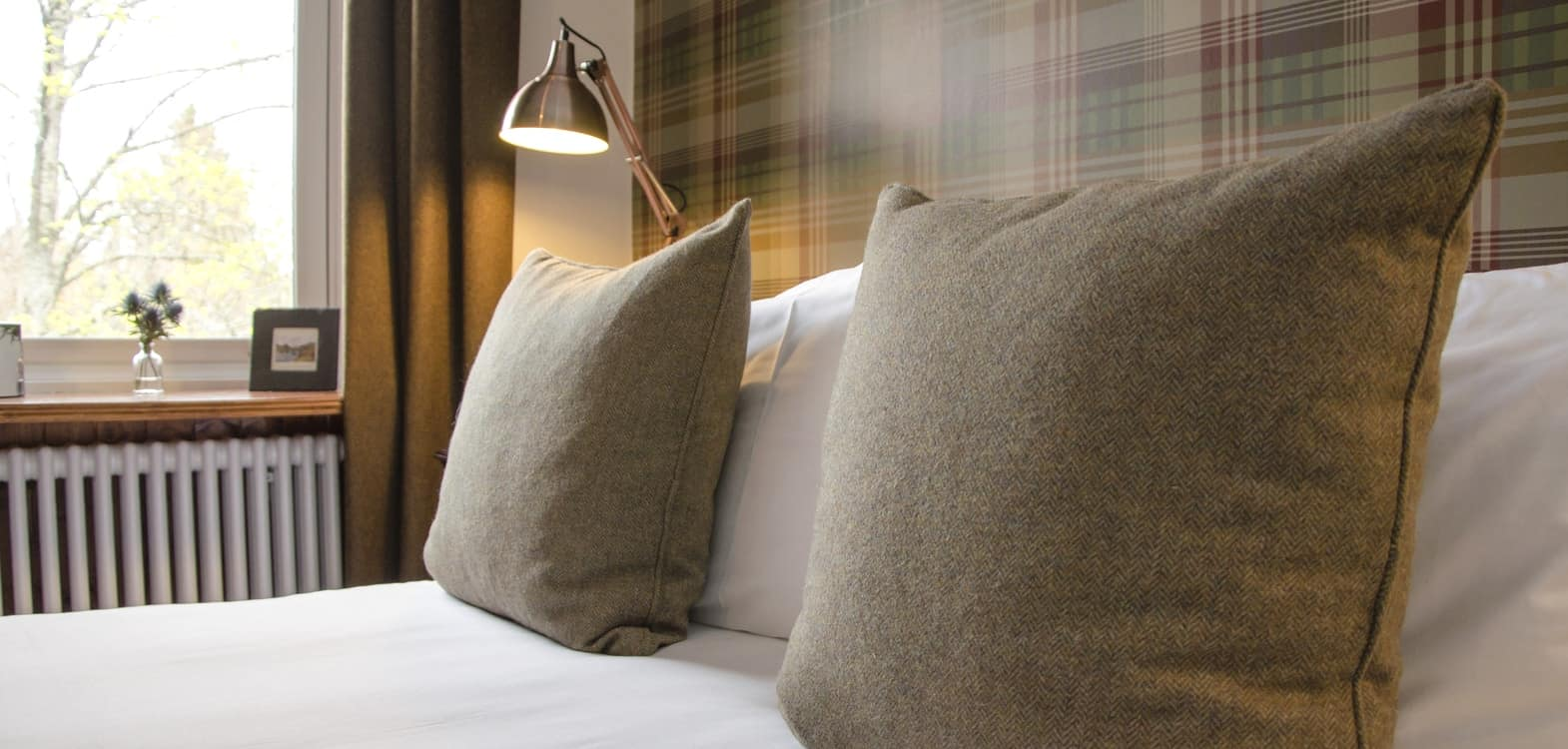 close up of natural colour wool covered cushions on a made up bed in Firhall B&B Scotland