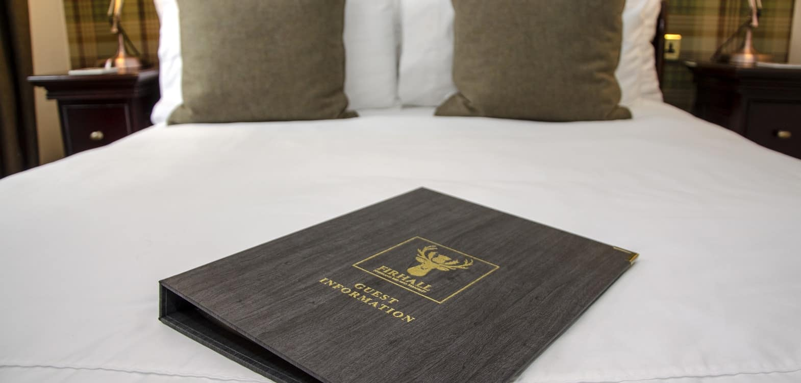 Firhall guest information folder laid out on a made up bed in the Skye bedroom