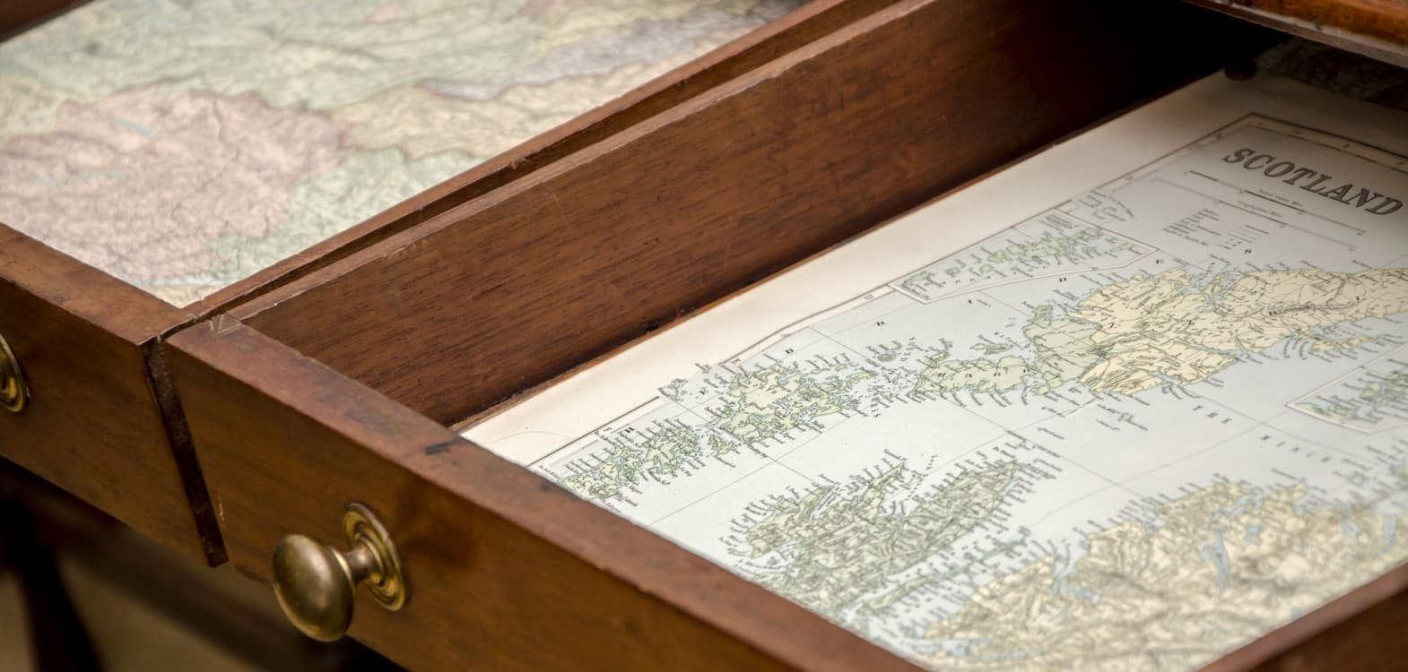 Dressing table drawers opened out to show maps of Scotland lining the draw bottoms at Firhall Bed & Breakfast in Scotland