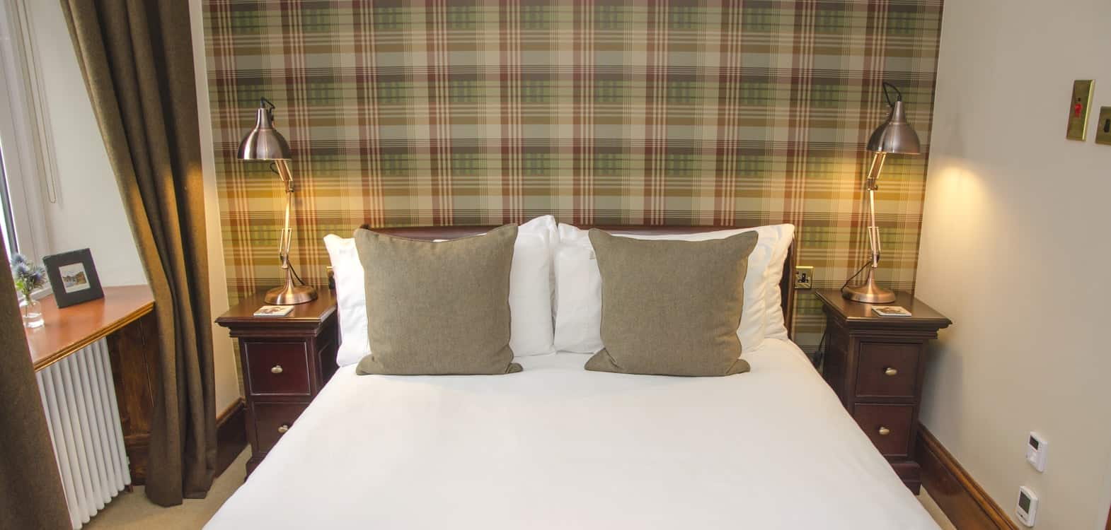 Mulberry tartan wallpaper behind a mahogany sleigh bed at Firhall Highland B&B