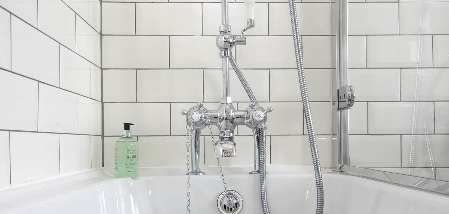 Close up of bath taps with controls for shower hose with Scottish Fine Soaps Sea Kelp shower gel