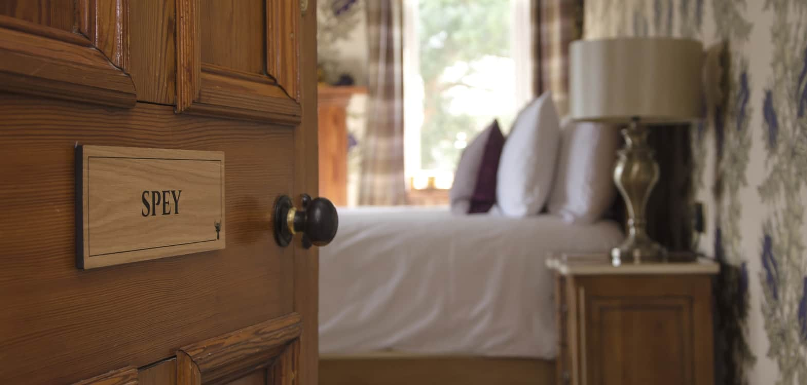 Open door with Spey door label leading into the room where there is a bed made up with white bedding